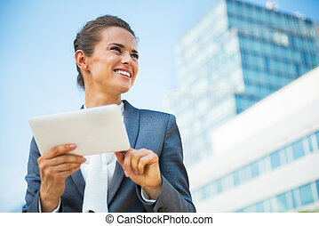 Happy business woman using tablet pc in front of office...