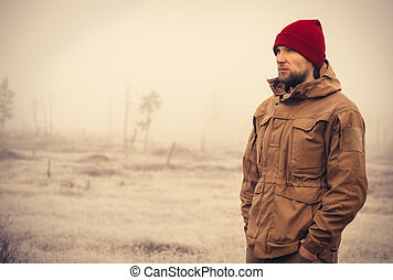 Young Man wearing winter hat clothing outdoor with foggy...