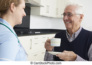 Nurse Chatting With Senior Man During Home Visit
