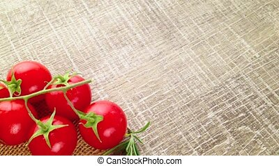 Closeup of bunch of wet tomatoes and rosemary on wooden...