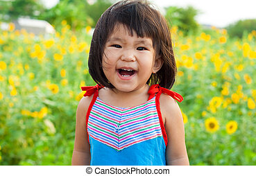 nice big smile from asian children on sunflower field