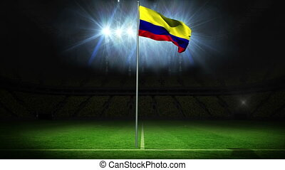 Colombia national flag waving on flagpole against football...