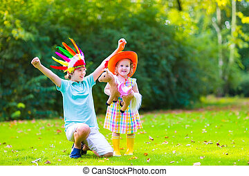 Kids playing cowboy - Two happy kids, laughing boy dressed...