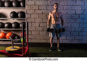 gym man holding hex dumbbells with muscles - gym man holding...