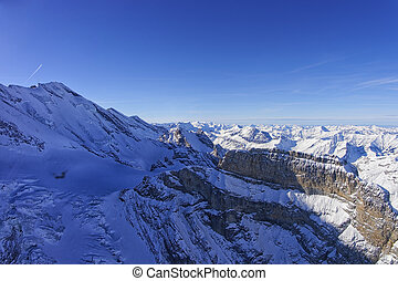 Coomb, wall and peak in Jungfrau region helicopter view in...