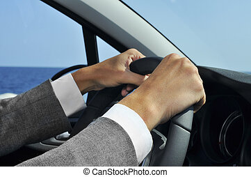 man in suit driving a car - closeup of a man in suit driving...