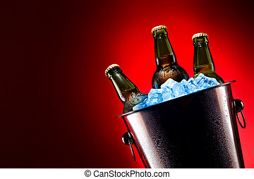 Beer bottles in ice bucket isolated on colored background