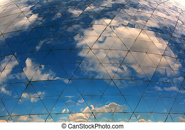 Clouds reflected in windows of modern round building.