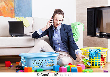 Mother organising toys and working - Young woman cleaning up...