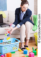 Young working mother organising toys - Young woman working...