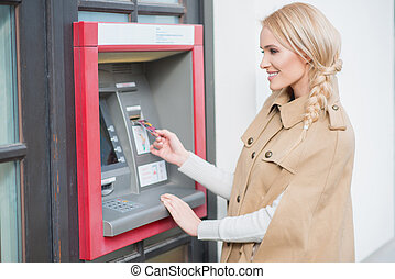 Pretty blond woman drawing money at an ATM standing outdoors...