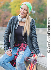 Laughing trendy young urban woman in raggedy designer jeans...