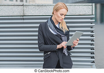Attractive woman using a tablet outdoors