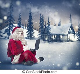 Santa Claus with laptop - Santa Claus surfs on internet with...