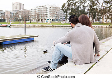 Couple hugging each other close to a lake