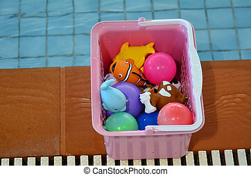 Water toy box beside swimming pool. Background texture....