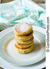 curds fritter with icing sugar on a white-blue dish on a...