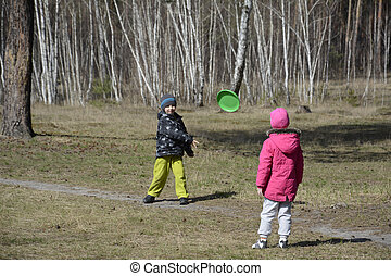 Boy with a girl playing in a clearing in the woods they throw th