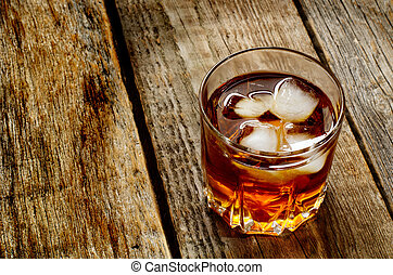 glass of whisky on a wood background