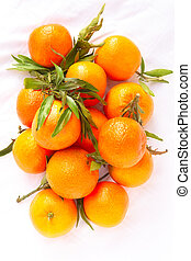 Clementines - Freshly picked clementines with leaves on...