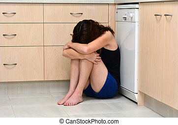 Woman domestic violence - Sad woman sit in her kitchen and...