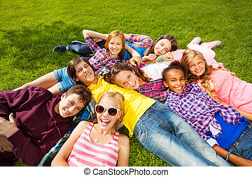 Happy children laying together on green grass