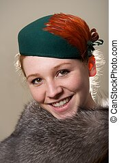 Smiling redhead in green hat and fur