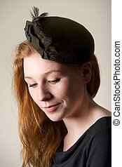 Smiling redhead in green hat with bow