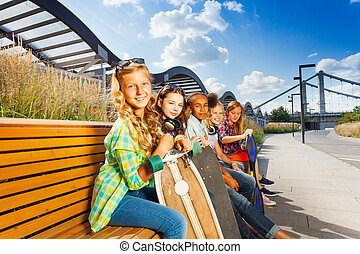 Kids sit on bench in summer with skateboards