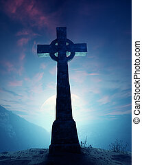 Celtic Cross with moonscape on crest of rocky mountain