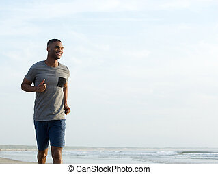 Active young man jogging at the beach - Active young man...