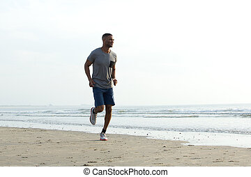 Young african man jogging at the beach. Healthy lifestyle