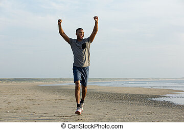 Man running on beach with arms outstretched celebrating