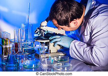 Man doing reseach - Man is looking into the glass of...