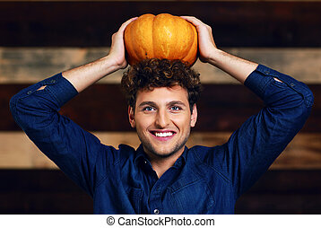 Portrait of a happy man with pumpkin on head