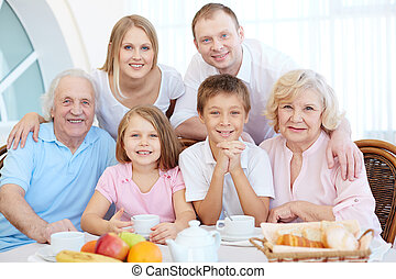 Family at dinner table - Portrait of happy senior and young...