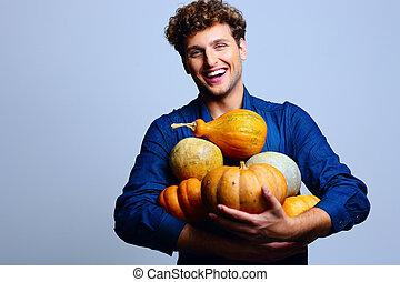 Smiling man holding pumpkins over blue background