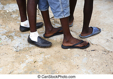 Feet of African men in different shoes waiting on a stony...
