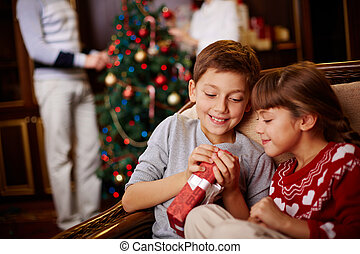 Curious siblings - Two siblings opening Christmas gift with...