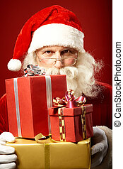Generous Santa - Santa Claus with pile of gifts looking at...