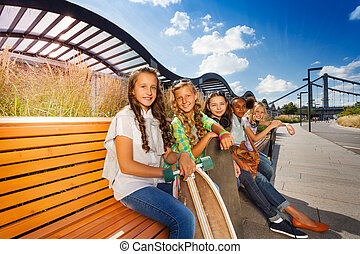 Happy friends sitting on wooden bench in a row