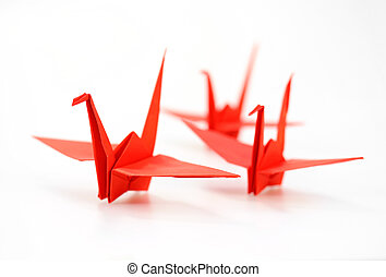 Traditional Japanese origami crane made of red paper over...