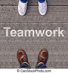 Two pairs of shoes standing on walkway with Teamwork