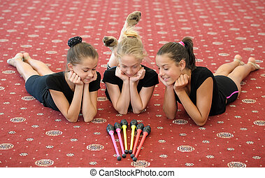 Three girls on the floor looking at Indian clubs - Three...