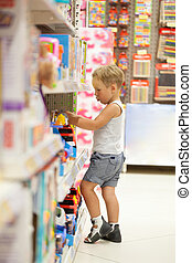 Boy watching cars in the toy shop - Little boy watching and...
