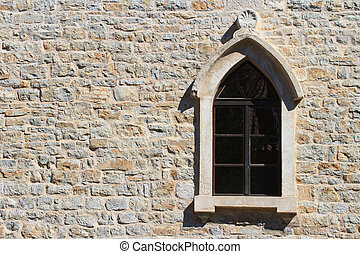 Window with an arch on the old wall in the city of Budva