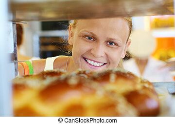 Happy woman looking at fresh bread in the shop