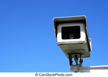 surveillance security camera against clear blue sky