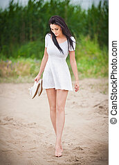 Young brunette strolling barefoot - Attractive brunette girl...