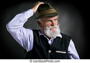 Old bavarian man in hat on black background - Portrait of...